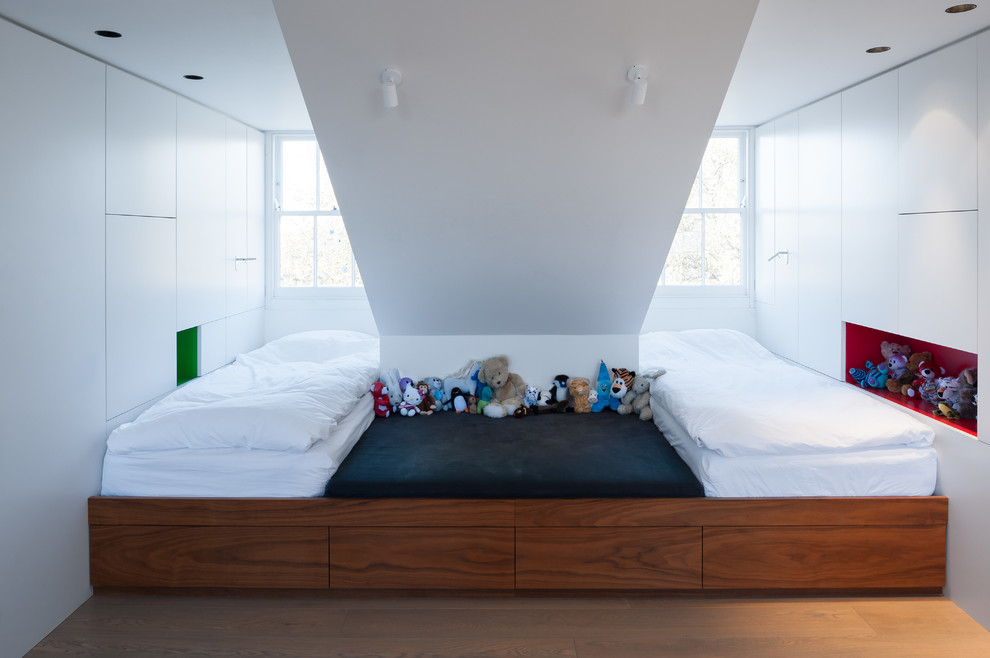 Kids' room - small contemporary gender-neutral light wood floor kids' room idea in London with white walls