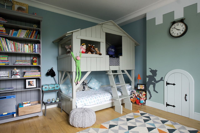 Mid-sized elegant boy medium tone wood floor kids' room photo in London with multicolored walls