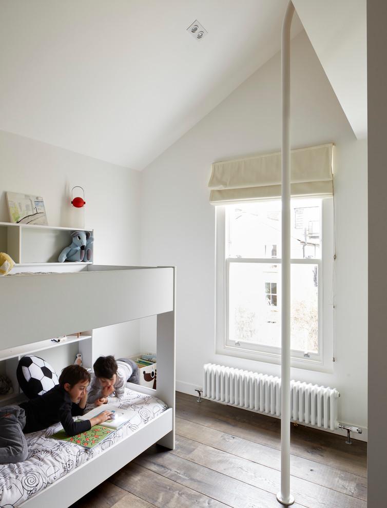 Large trendy medium tone wood floor kids' bedroom photo in London with white walls