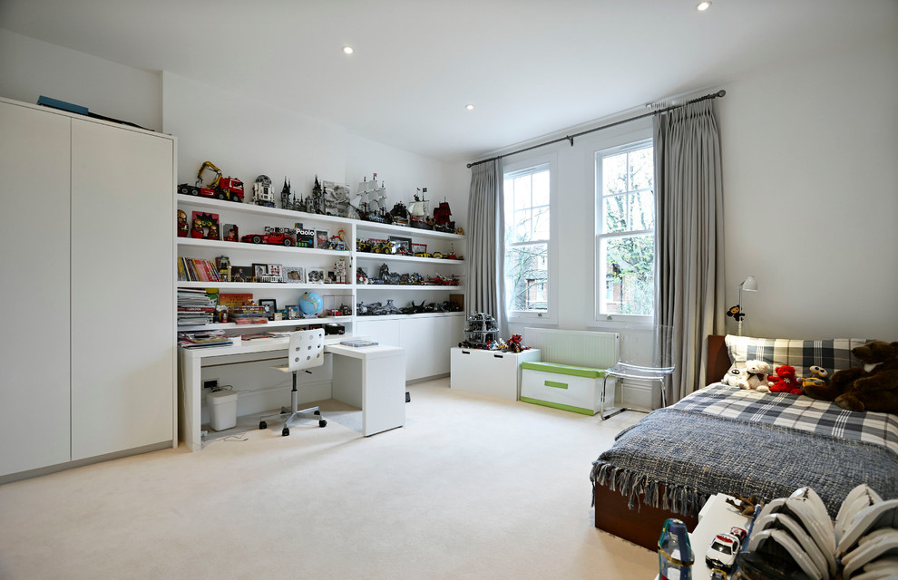 Large trendy boy carpeted kids' room photo in London with white walls
