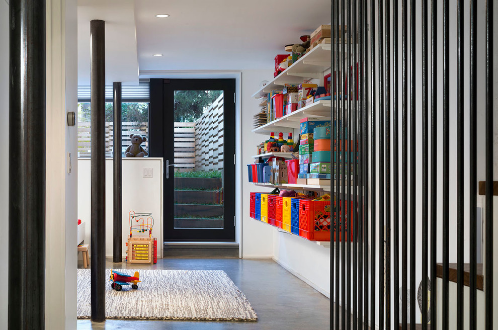 Example of a trendy concrete floor playroom design in New York with white walls