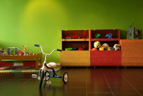 bicycle in the middle of a playroom with a green wall