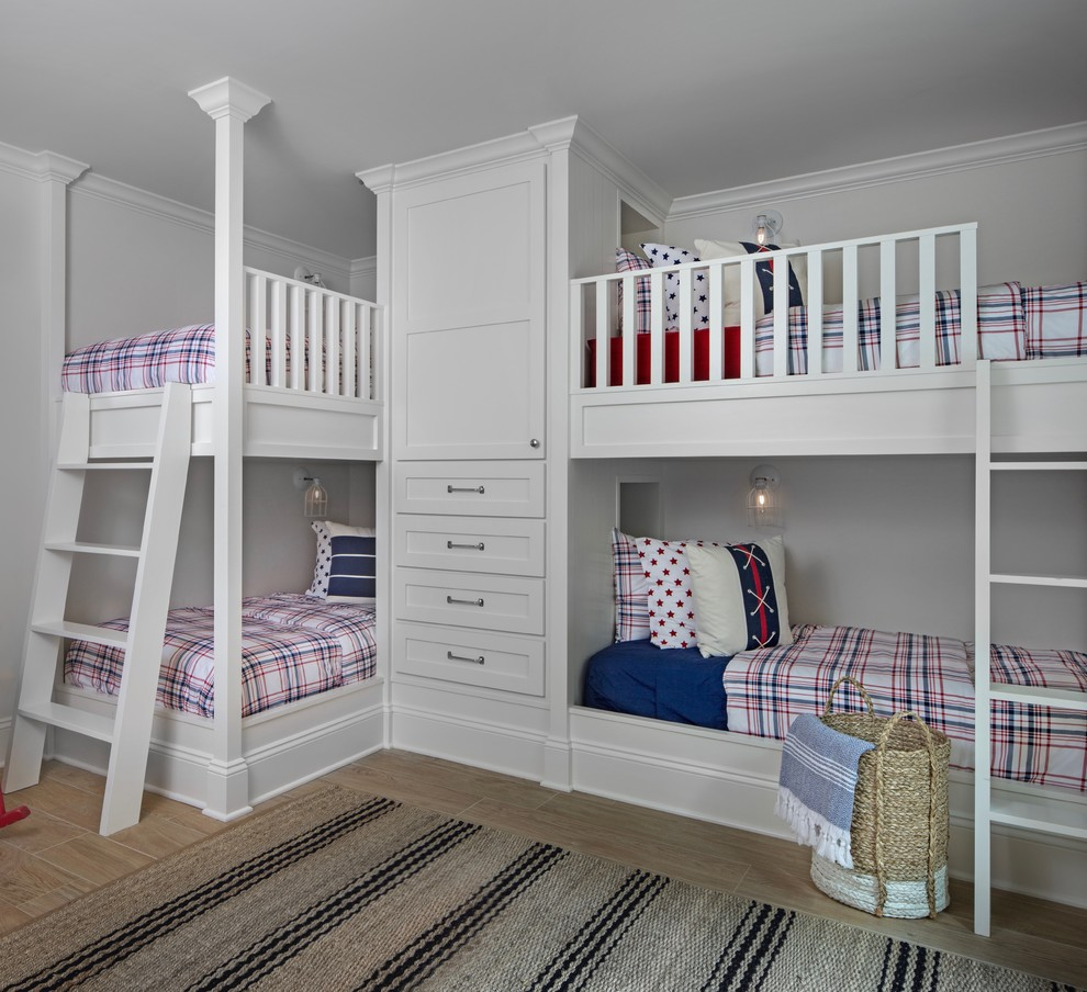 Beach style gender-neutral light wood floor kids' room photo in Other with white walls