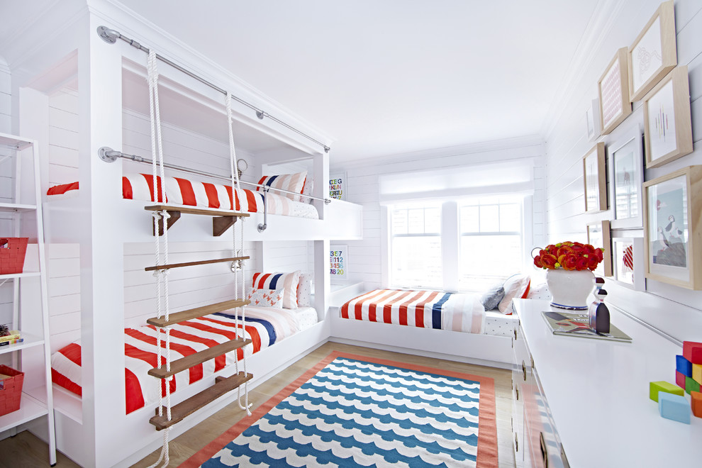 Mid-sized beach style gender-neutral light wood floor kids' room photo in New York with white walls