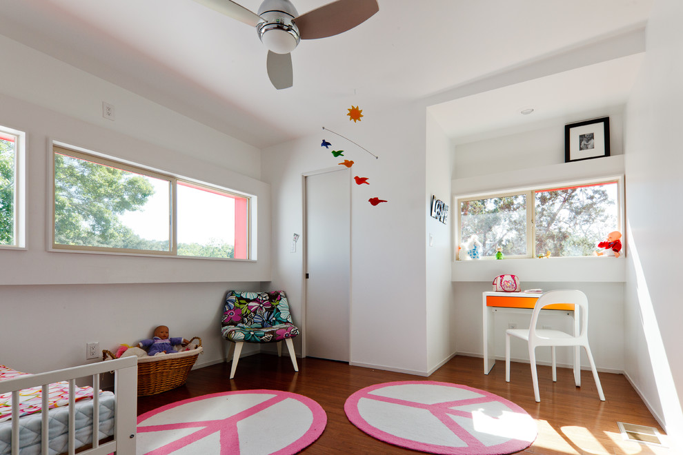 Example of a minimalist kids' room design in Austin with white walls