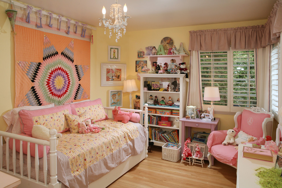 Example of a trendy girl light wood floor kids' room design in Los Angeles with yellow walls