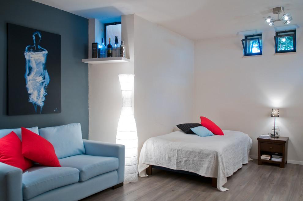 Example of a trendy gender-neutral light wood floor kids' room design in Tel Aviv with white walls
