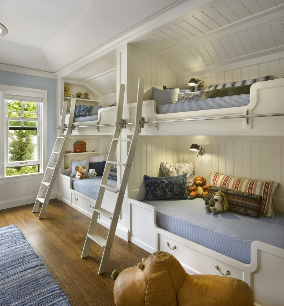 Elegant gender-neutral medium tone wood floor kids' bedroom photo in Chicago with blue walls