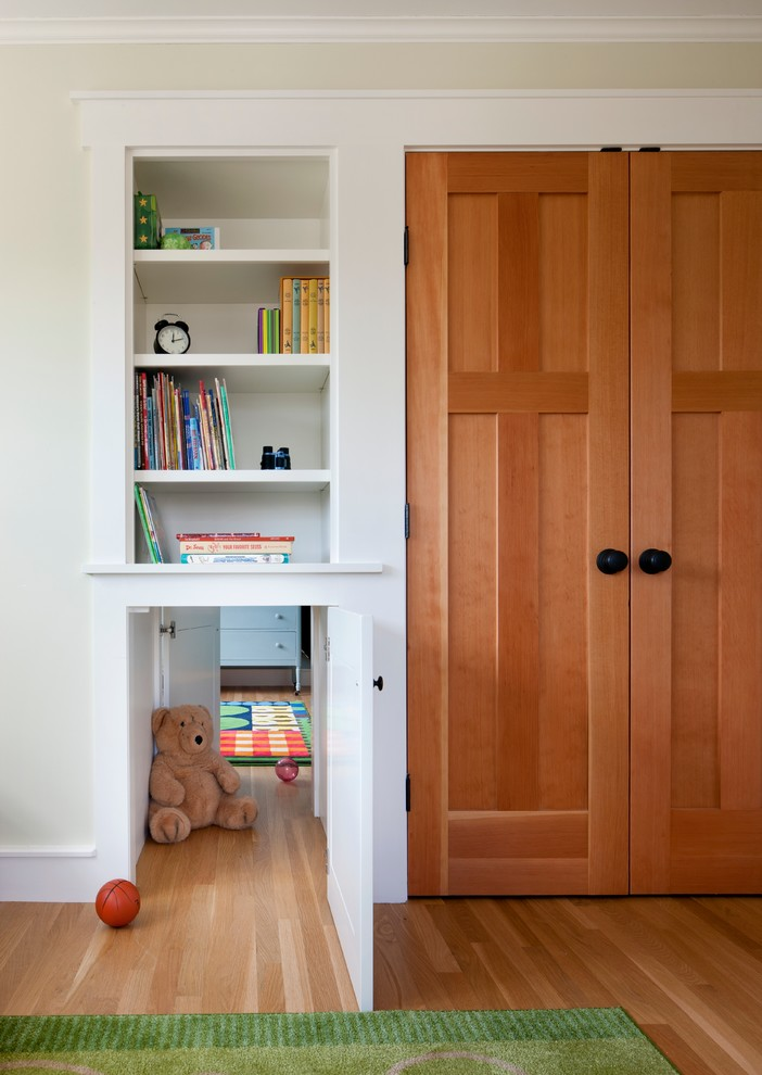 Example of a classic gender-neutral light wood floor kids' room design in Boston with yellow walls