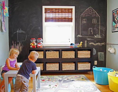 niños jugando en su cuarto de juegos con pizarra y alfombra de juegos