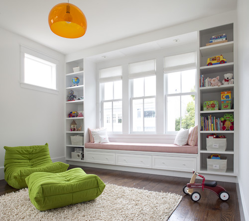 Bay windows with pink cushion seating flanked by tall shelves