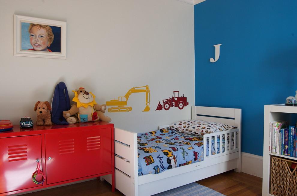 Example of a trendy boy medium tone wood floor kids' room design in San Francisco with multicolored walls