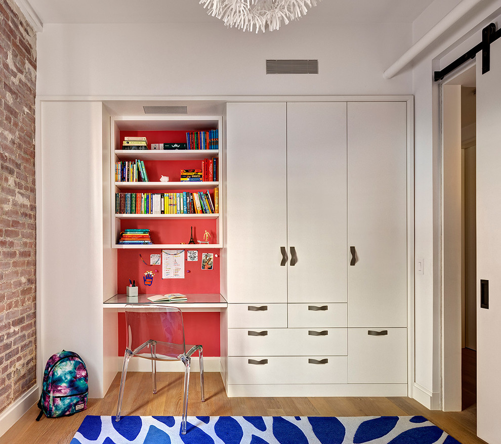 Example of a small urban gender-neutral light wood floor kids' room design in New York with red walls