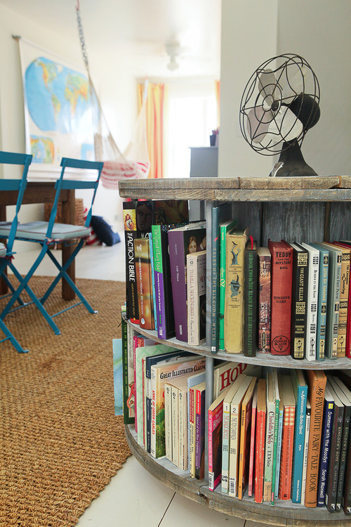 reading room with wire reel book holder with old fan and blue chairs and map