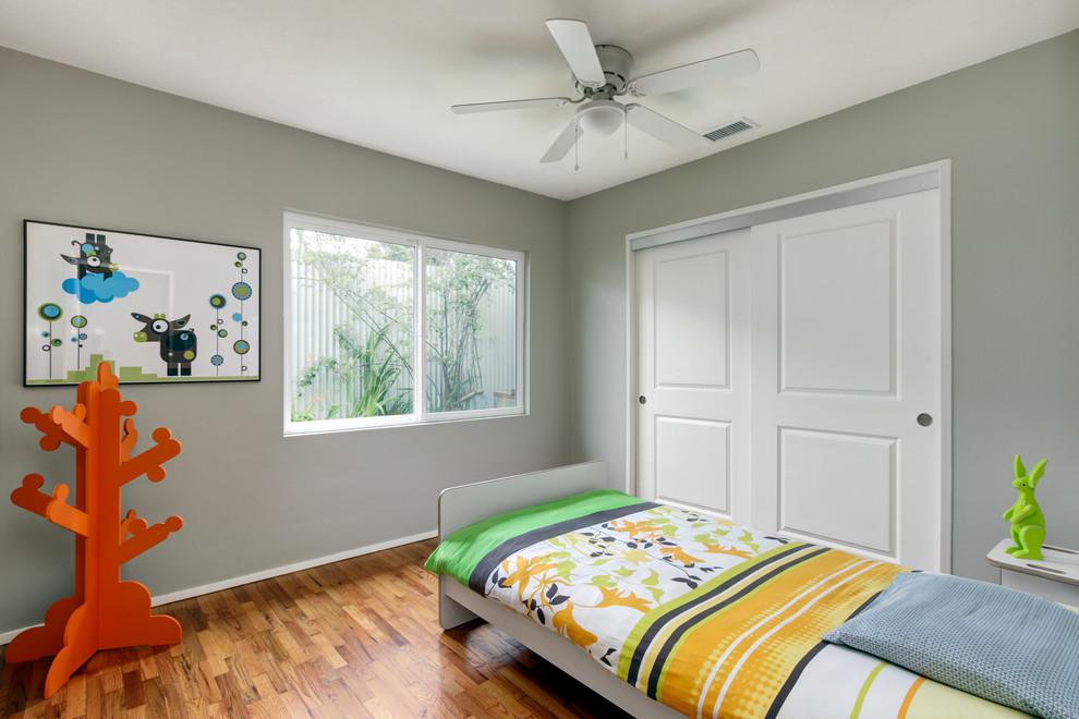 Kids' room - mid-sized modern boy medium tone wood floor kids' room idea in San Diego with gray walls