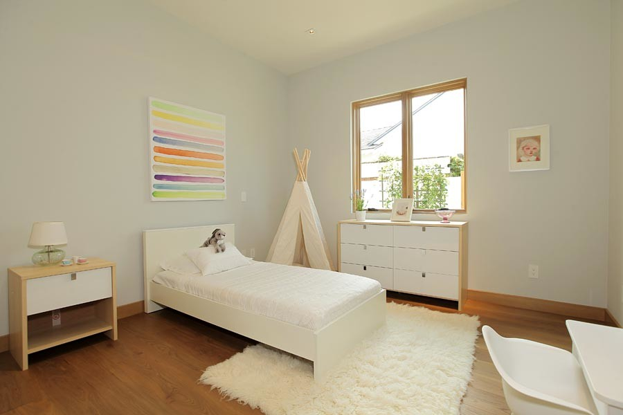 Mid-sized mid-century modern girl medium tone wood floor kids' room photo in Los Angeles with white walls