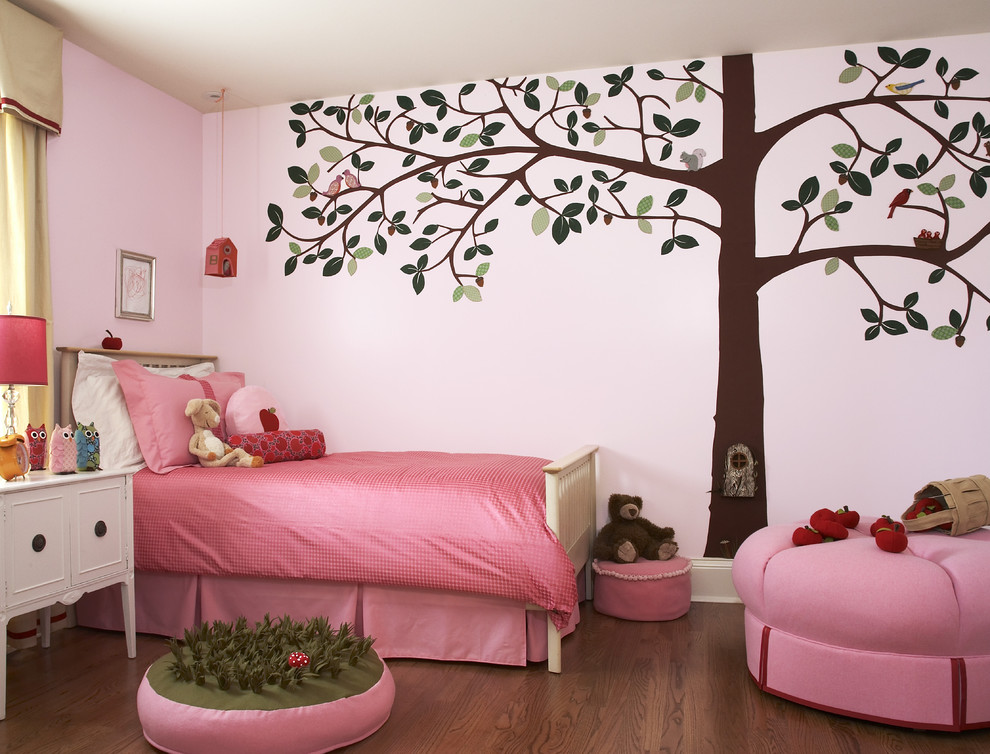 Transitional girl medium tone wood floor kids' room photo in Chicago with pink walls