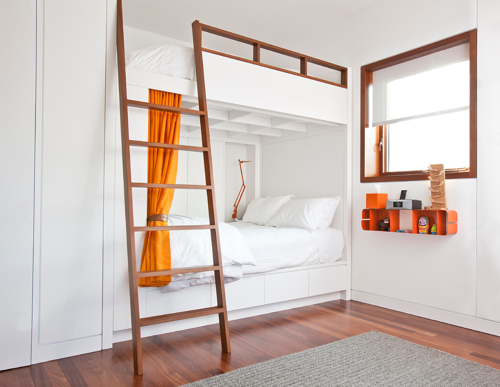 Example of an urban gender-neutral medium tone wood floor and brown floor kids' room design in Chicago with white walls