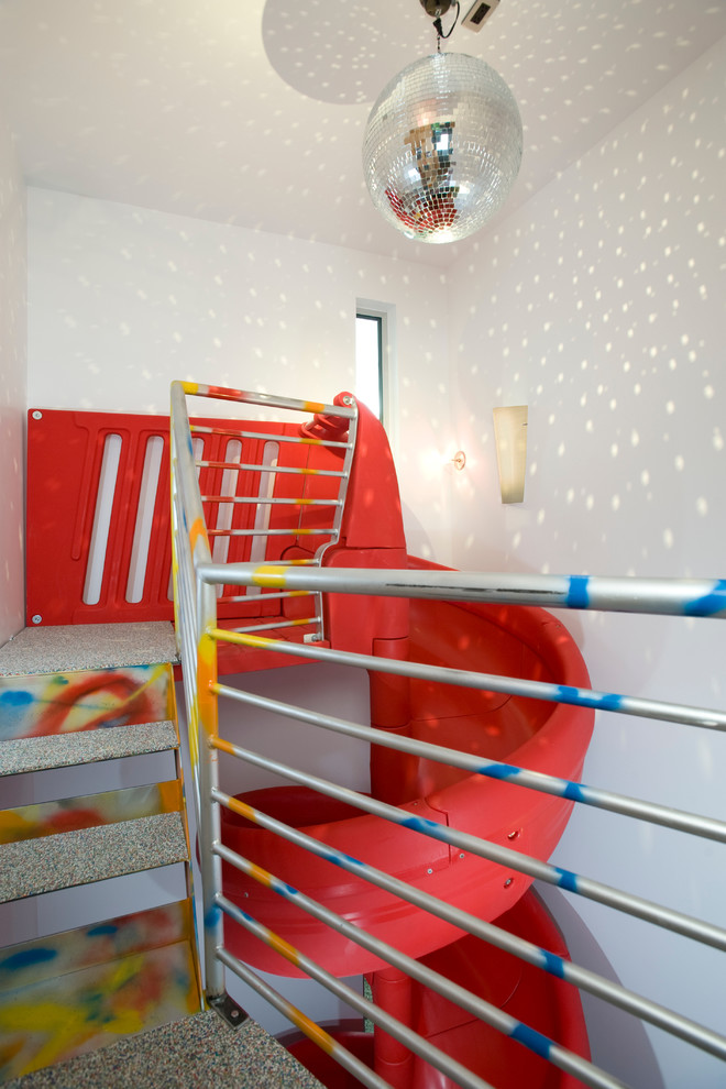 Trendy gender-neutral playroom photo in Denver with white walls