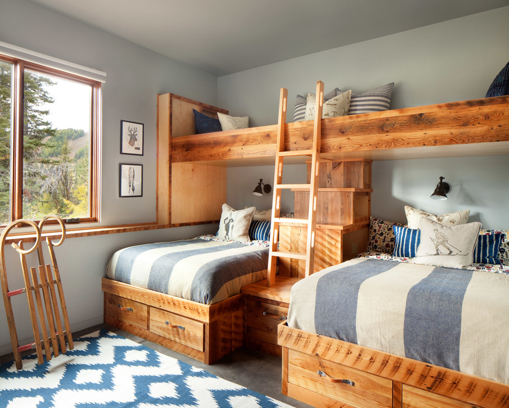 Example of a mid-sized mountain style gender-neutral concrete floor and gray floor kids' bedroom design in Other with gray walls