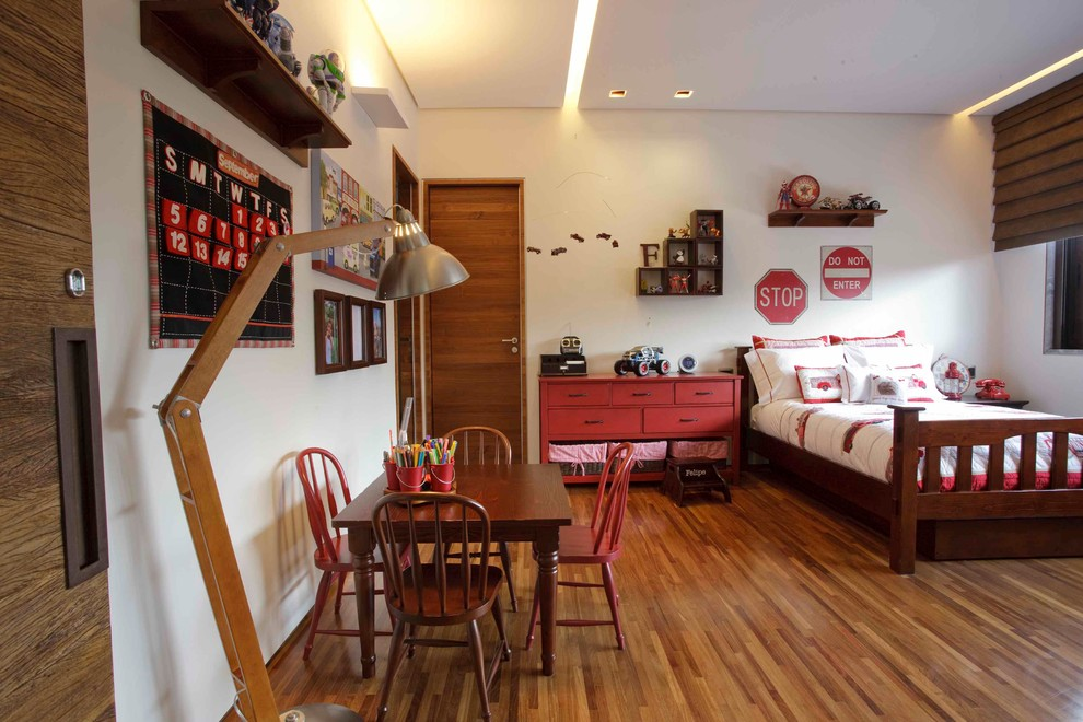 Example of an island style gender-neutral medium tone wood floor kids' room design in Other with white walls
