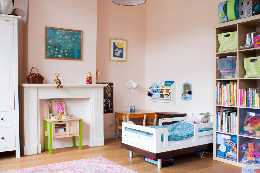 Example of a large eclectic girl medium tone wood floor kids' room design in Amsterdam with pink walls