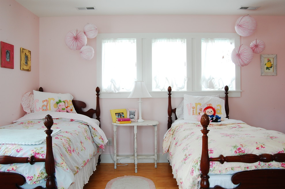 Example of a mountain style girl medium tone wood floor kids' bedroom design in New York with pink walls