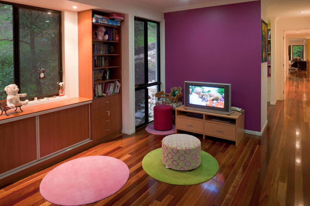 This is an example of a small contemporary kids' room for kids 4-10 years old and girls in Brisbane with purple walls and medium hardwood floors.