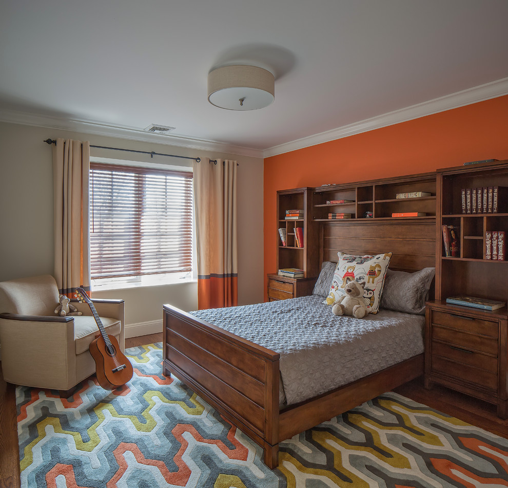 Example of a large transitional boy medium tone wood floor and brown floor kids' room design in New York with orange walls