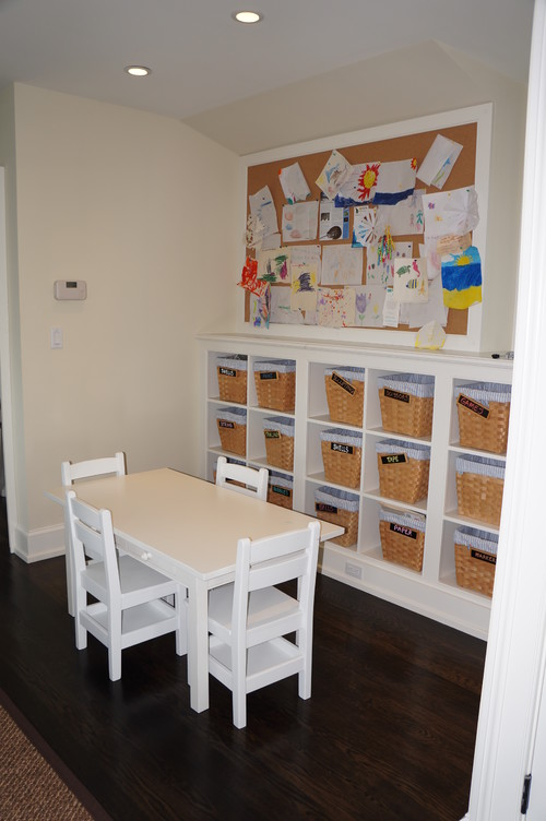 Learning corner with table and chairs, a bulletin board, and cubbies with baskets