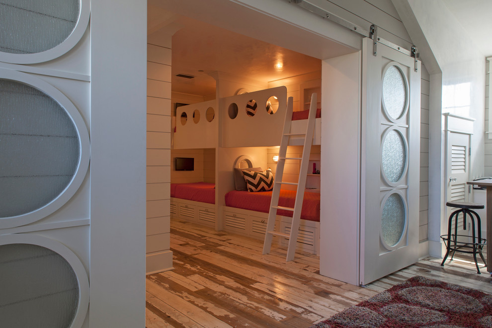 Transitional gender-neutral light wood floor kids' room photo in Miami with white walls