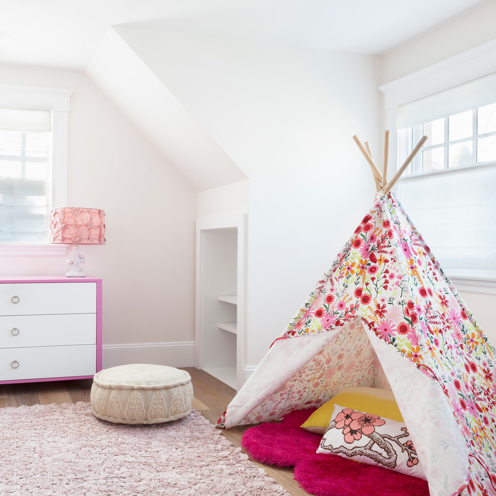 Example of a beach style girl medium tone wood floor and beige floor kids' room design in New York with white walls