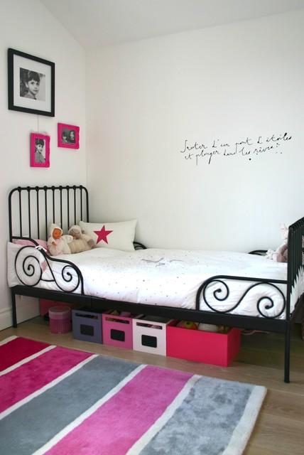 Design ideas for a classic toddler's room for girls in London with white walls and light hardwood flooring.