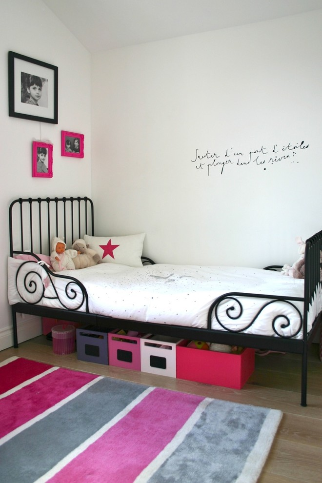 Example of a transitional girl light wood floor kids' room design in London with white walls
