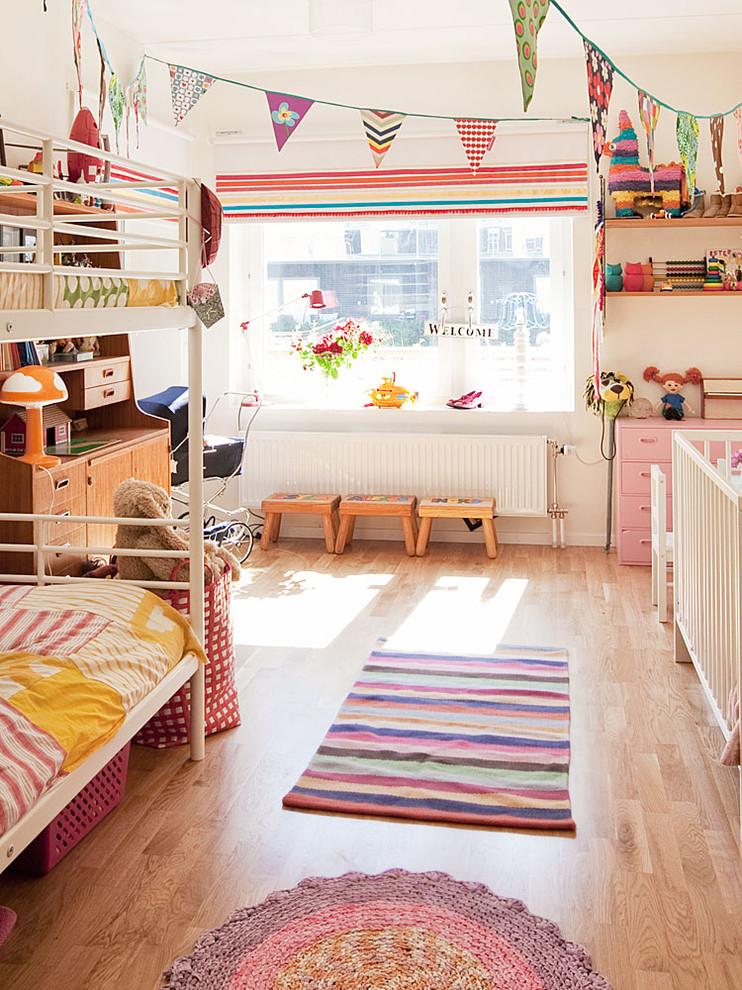 Large danish girl light wood floor kids' bedroom photo in Stockholm with white walls
