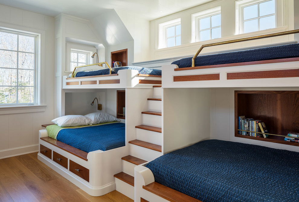 Example of a beach style boy medium tone wood floor kids' room design in New York with white walls