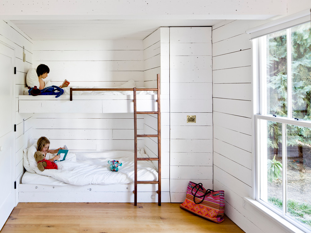Country gender-neutral medium tone wood floor kids' room photo in Portland with white walls
