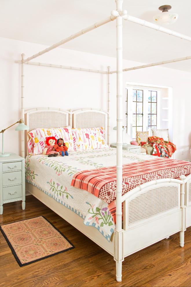 Kids' room - large country girl medium tone wood floor and brown floor kids' room idea in Los Angeles with pink walls