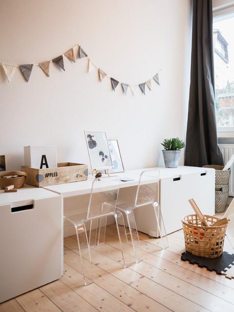 Example of a small danish gender-neutral light wood floor and beige floor kids' room design in Berlin with white walls