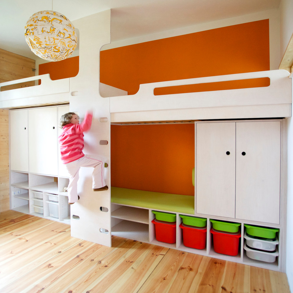 Kids' room - large contemporary gender-neutral medium tone wood floor kids' room idea in Other with orange walls