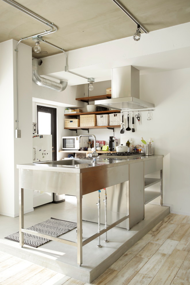Example of a small urban kitchen design in Tokyo with an integrated sink, open cabinets and an island