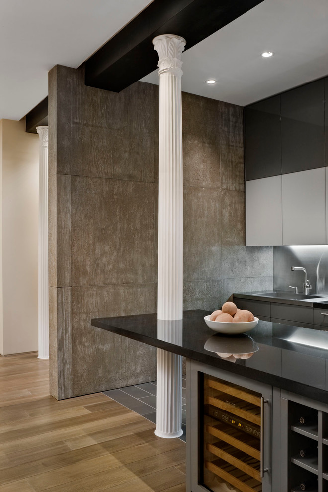 Kitchen - contemporary kitchen idea in New York with flat-panel cabinets and metallic backsplash
