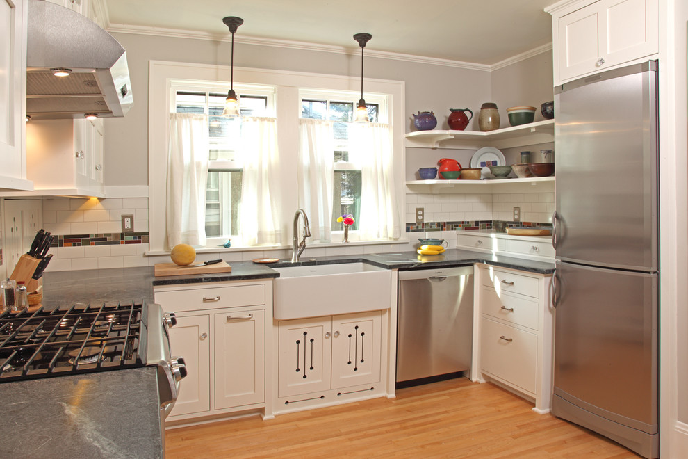 Inspiration for a small craftsman u-shaped light wood floor and brown floor enclosed kitchen remodel in Minneapolis with a farmhouse sink, white cabinets, stainless steel appliances, recessed-panel cabinets, white backsplash, subway tile backsplash, no island and soapstone countertops