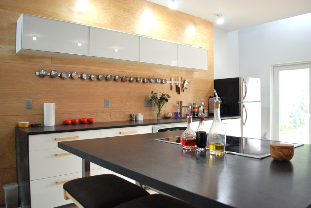 Kitchen - industrial kitchen idea in Philadelphia with solid surface countertops, flat-panel cabinets and white cabinets