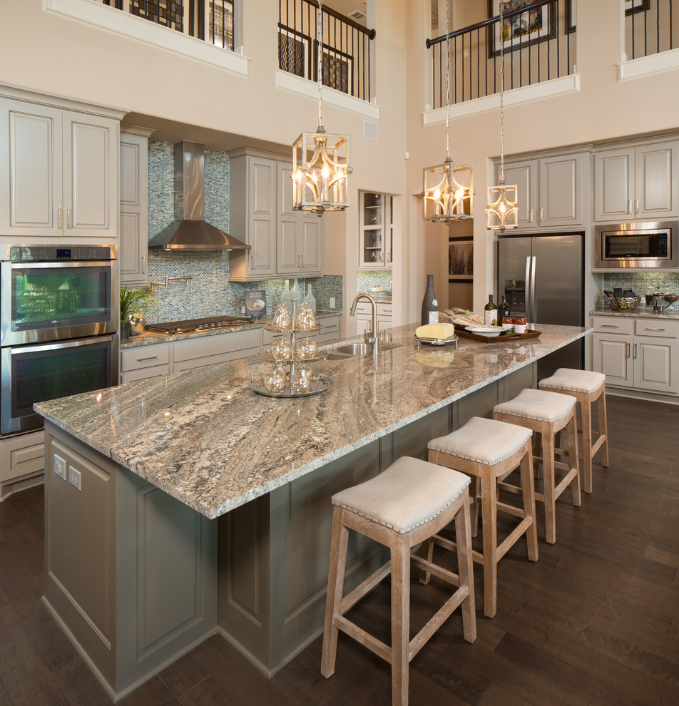 Inspiration for a transitional l-shaped dark wood floor kitchen remodel in Austin with an undermount sink, raised-panel cabinets, gray cabinets, blue backsplash, mosaic tile backsplash, stainless steel appliances, an island and gray countertops