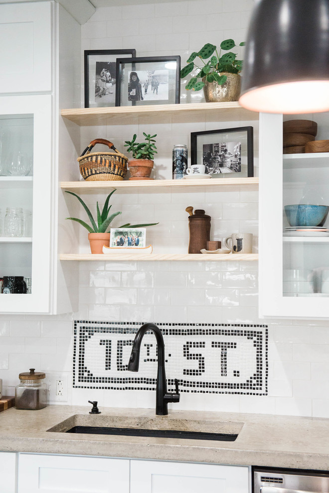 Example of a small eclectic single-wall slate floor and gray floor kitchen pantry design in New York with an undermount sink, glass-front cabinets, white cabinets, concrete countertops, white backsplash, ceramic backsplash, stainless steel appliances and an island