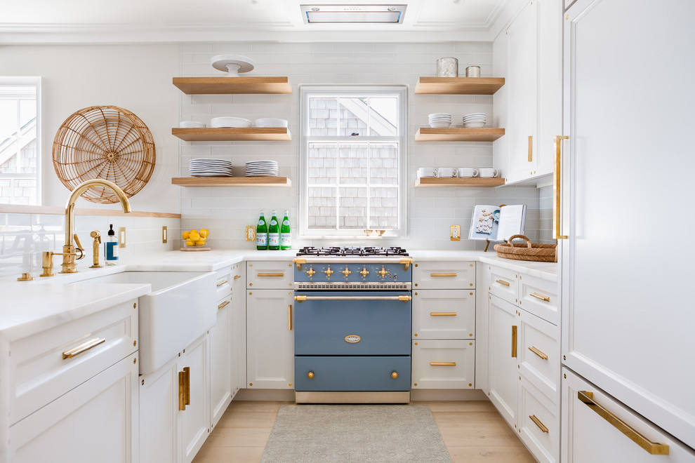 Example of a beach style u-shaped light wood floor enclosed kitchen design in Boston with a farmhouse sink, recessed-panel cabinets, white cabinets, white backsplash, subway tile backsplash, colored appliances and no island