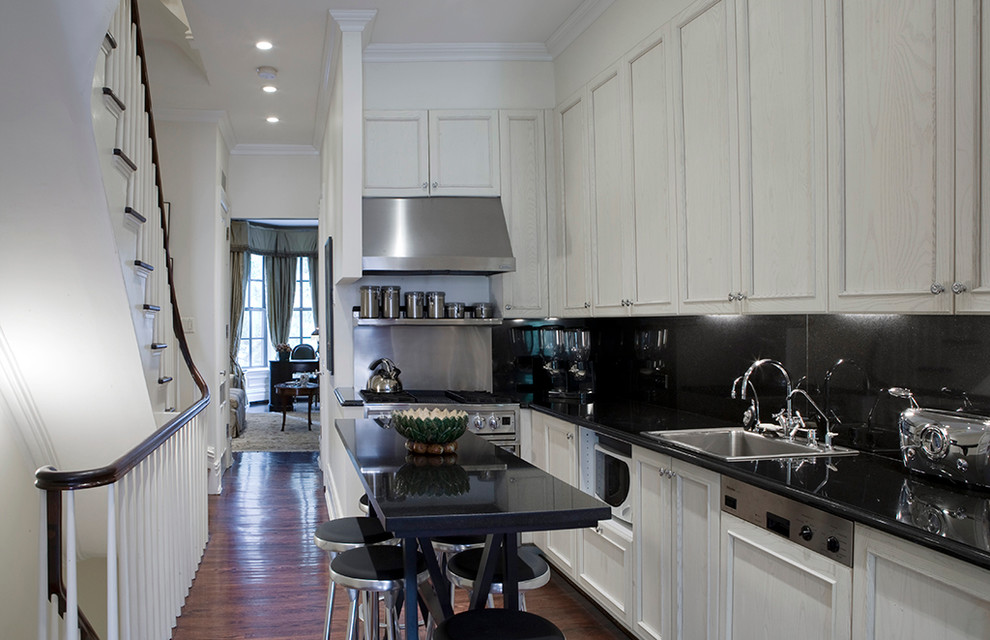 Kitchen - traditional l-shaped dark wood floor kitchen idea in New York with a drop-in sink, recessed-panel cabinets, light wood cabinets, black backsplash, glass sheet backsplash and stainless steel appliances