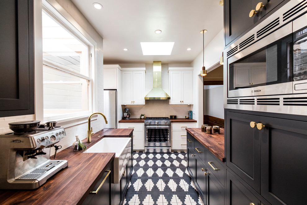 Kitchen - small transitional u-shaped kitchen idea in San Francisco with a farmhouse sink, shaker cabinets, black cabinets, wood countertops, white backsplash, stainless steel appliances, a peninsula and subway tile backsplash