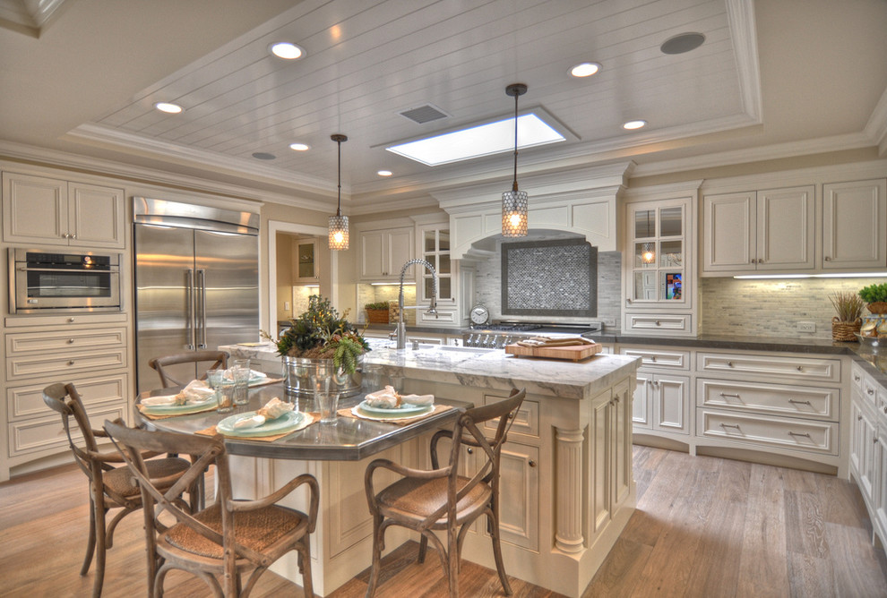 Beach style kitchen photo in Los Angeles with stainless steel appliances and marble countertops